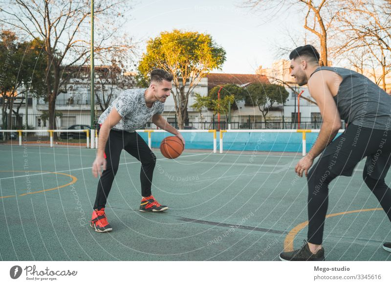 Two young friends playing basketball. Lifestyle Joy Happy Relaxation Leisure and hobbies Playing Sports Ball Human being Masculine Boy (child) Man Adults