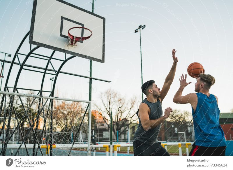 Young basketball players playing one-on-one on outdoor court. Joy Happy Relaxation Leisure and hobbies Playing Sports Ball Human being Masculine Boy (child) Man