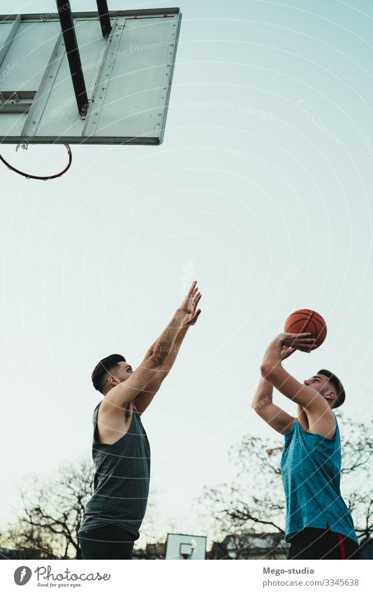 Young basketball players playing one-on-one. Joy Happy Relaxation Leisure and hobbies Playing Sports Ball Human being Masculine Boy (child) Man Adults