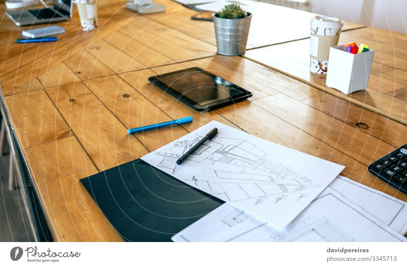 Workplace of an architect with blueprints and sketches Design Decoration Desk Table Office Business Notebook Plant Architecture Pen Wood Modern Creativity