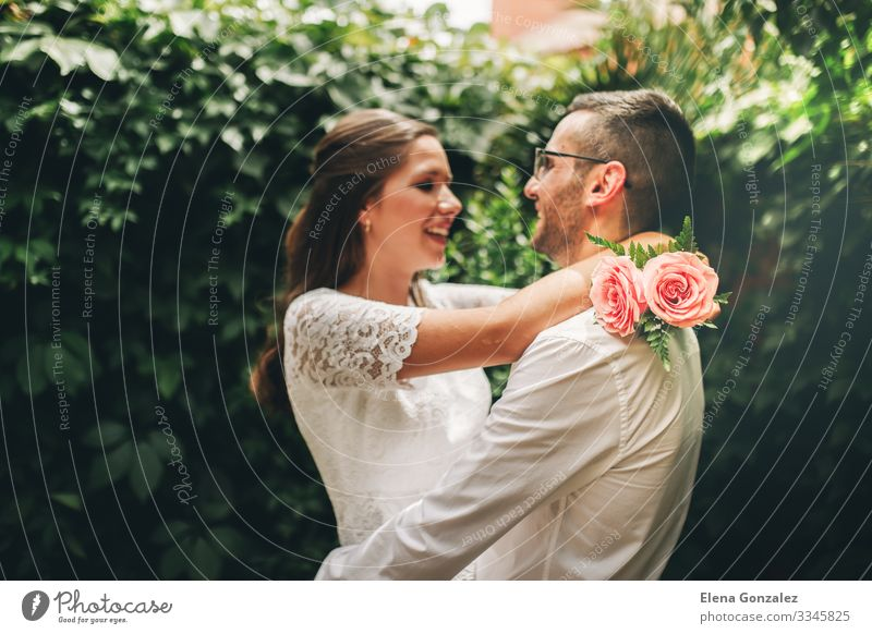Newlywed couple looking at each other hugging and dancing. Garden Feasts & Celebrations Wedding Woman Adults Man Rose Bouquet Kissing Love Embrace Emotions