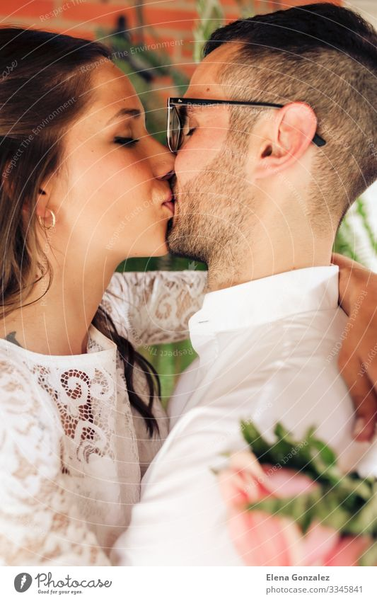 newlywed couple with close eyes and kissing Feasts & Celebrations Wedding Woman Adults Man Fingers Rose Bouquet Kissing Love Emotions Romance Eternity Tradition