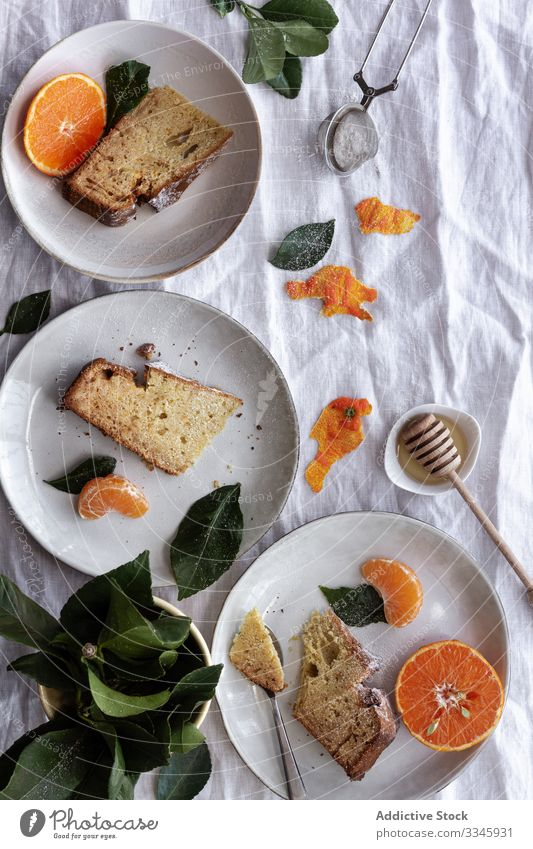 Sliced cake and citruses on plates on table tangerine fruit dessert sliced portion eating orange sweet mandarin pastry gourmet delicious cookie creative healthy