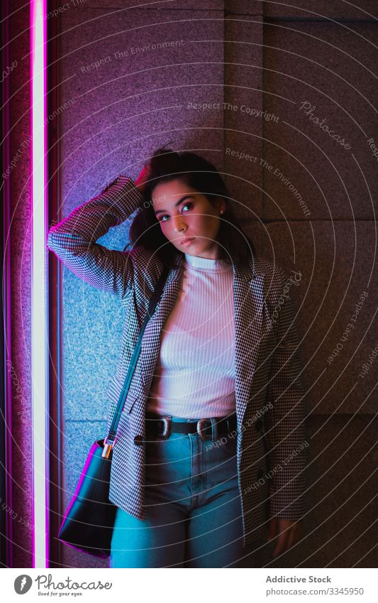 Young woman in casual outfit in neon light style clothing standing shaking head hair waving fashionable hipster millennial teenager city street urban lifestyle