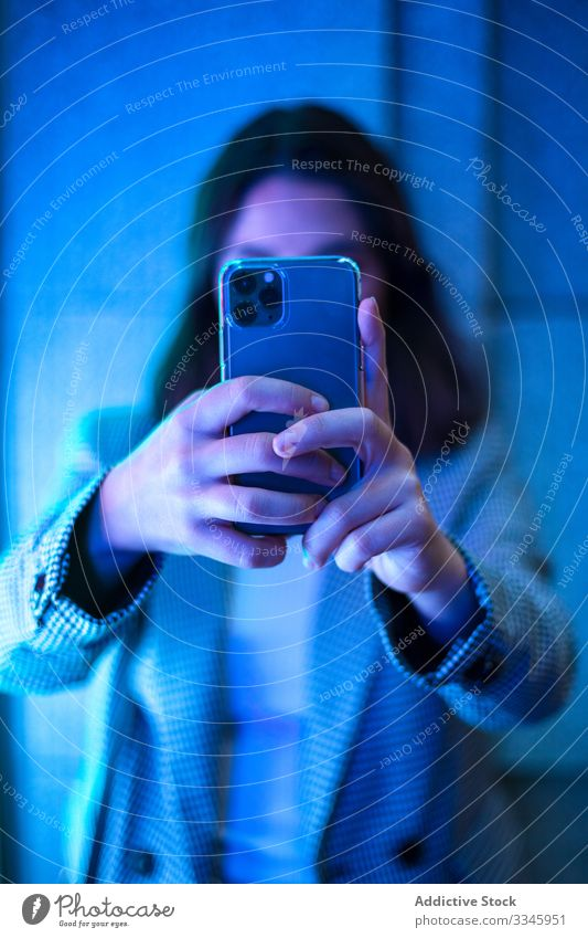 Contemporary faceless lady taking photo on smartphone woman shooting hands using mobile device gadget neon light female casual hipster millennial modern camera