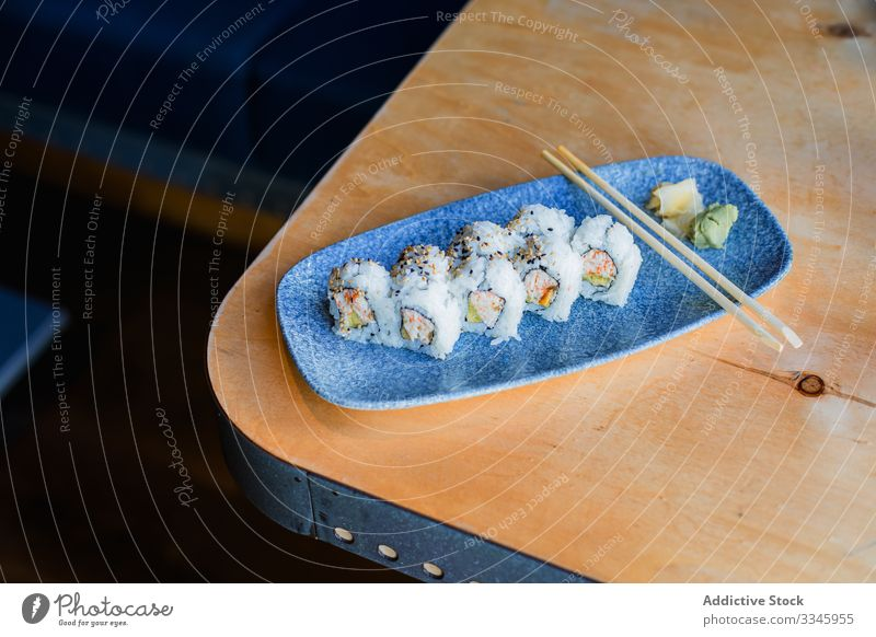 Fresh sushi with chopsticks on table asian food cuisine dish rice wooden ginger wasabi sesame dinner traditional seafood plate lunch restaurant roll meal fish