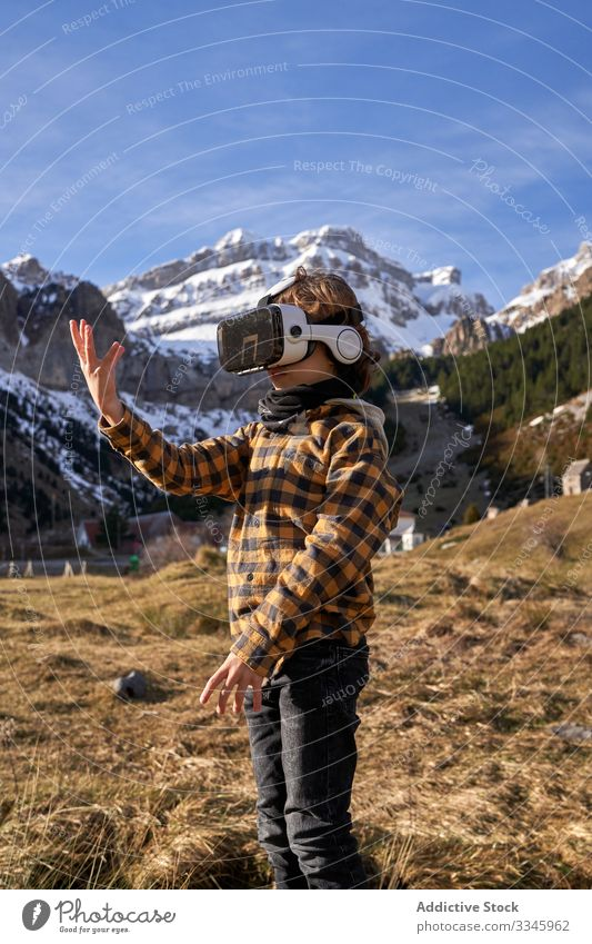 Boy standing on stone in VR glasses against mountain boy vr nature valley virtual reality headset modern device entertainment explore terrain technology digital