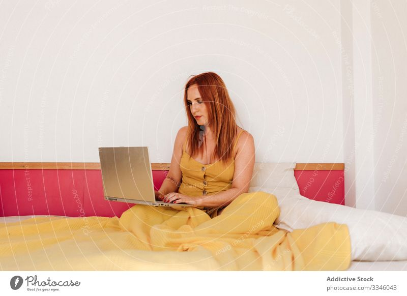 Woman working laptop on bed at home woman using browsing freelance lying morning busy smart yellow gown dress female lifestyle young internet sitting online
