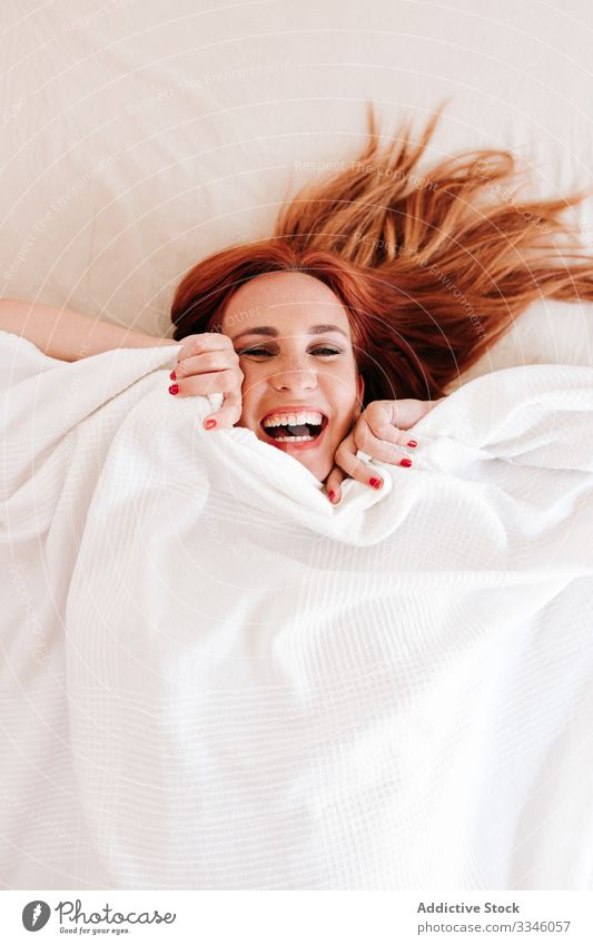 Positive lady hiding under blanket at home woman lying bed morning sitting cover fun relax rest smile enjoy playful redhead lifestyle young beautiful female