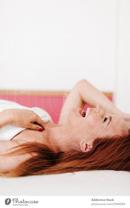 Positive lady lying down in bet at home woman bed hiding blanket morning sitting cover fun under relax rest smile enjoy playful redhead lifestyle young