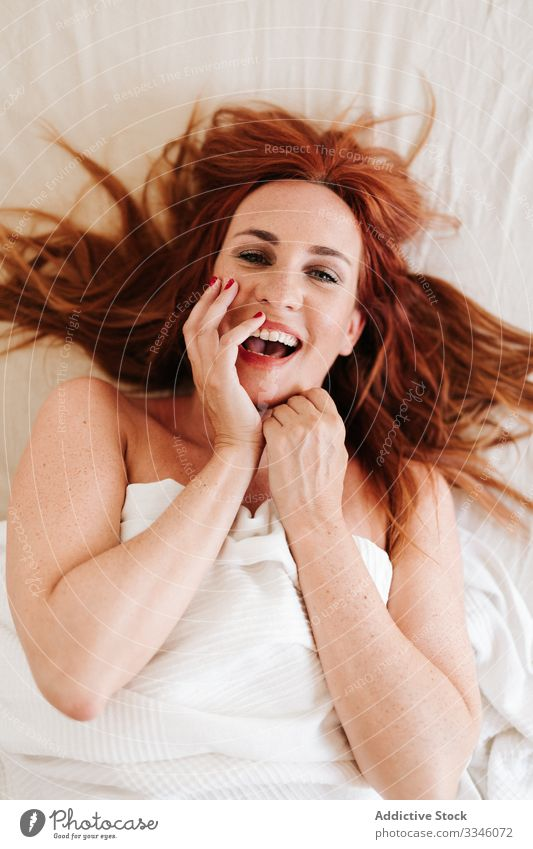 Positive lady hiding under blanket at home woman lying bed morning sitting cover yellow fun relax rest smile enjoy playful redhead lifestyle young beautiful