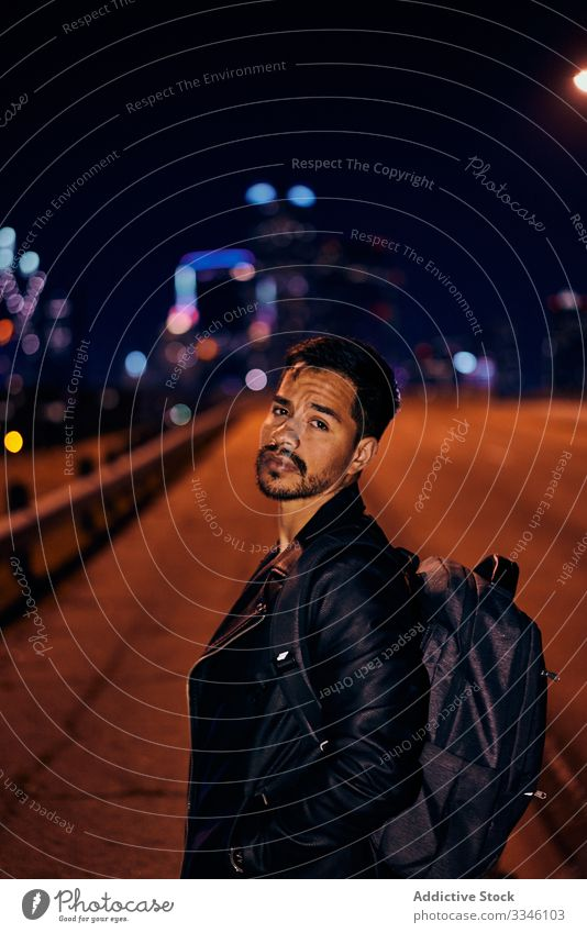 Confident Hispanic guy in stylish clothing at night city man street sidewalk backpack jacket leather urban modern male lifestyle young downtown handsome dusk