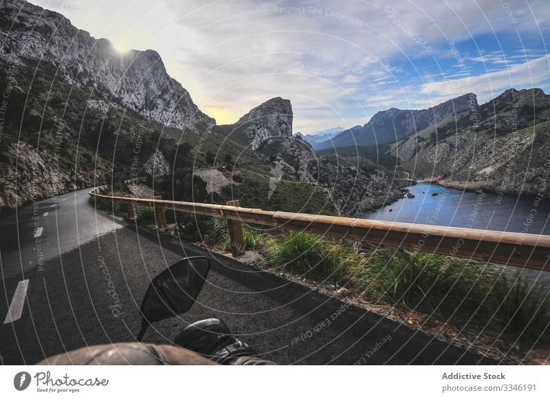 Faceless tourist riding motorbike on road surrounded by mountains man ride travel canyon lake landscape trip male tourism rock nature valley asphalt water