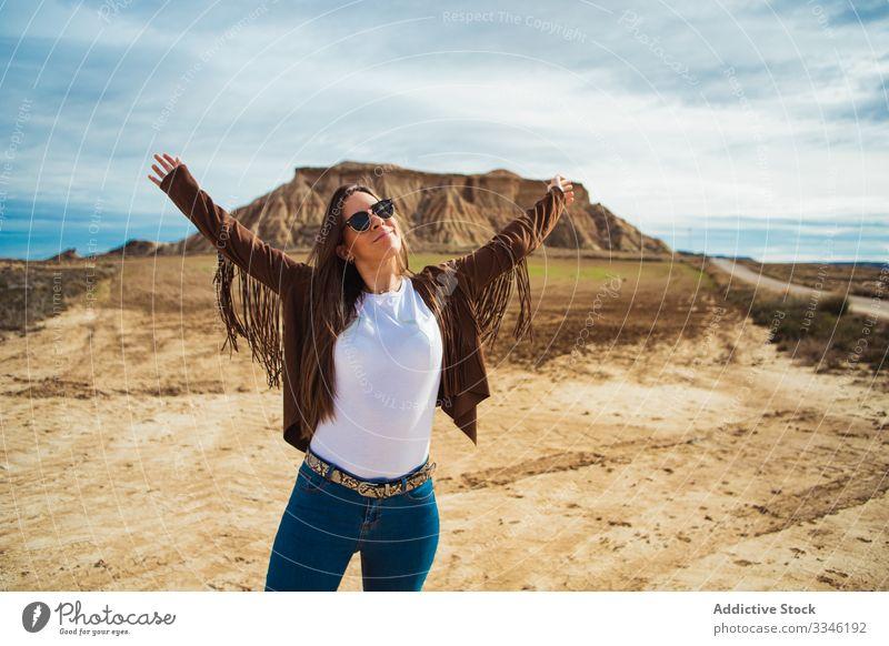 Joyful female tourist enjoying trip in desert woman travel vacation smile raised hands casual stylish sunglasses summer tourism blue sky nature lifestyle
