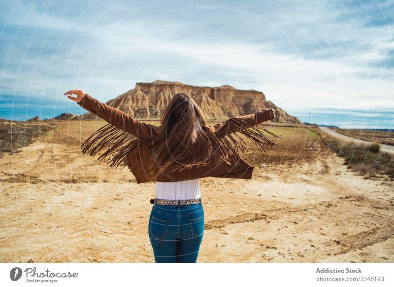Unrecognizable female enjoying trip in desert woman travel vacation raised hands casual stylish summer tourism blue sky nature lifestyle holiday young landscape