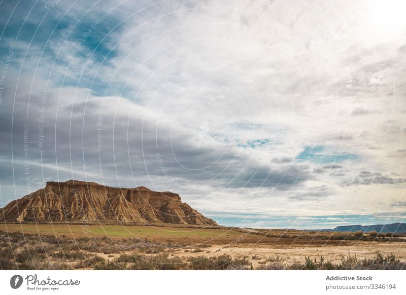 Tranquil landscape of empty valley and mountain desert shrub blue sky cloud scenic bardenas reales navarre spain nature sun summer rural trip travel countryside