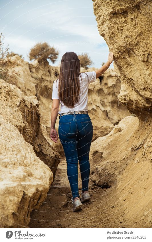 Anonymous female tourist exploring deserted terrain with cliffs travel canyon woman stone passage tourism activity extreme casual sky nature environment