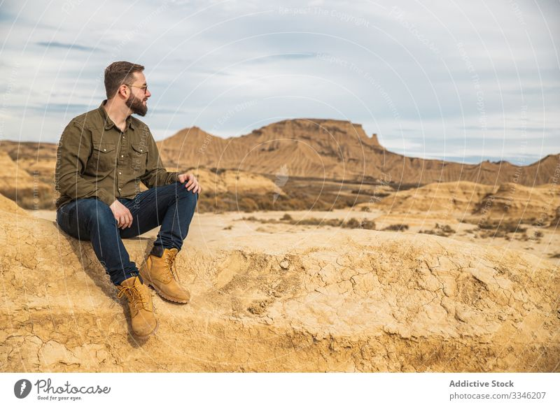 Young man on vacation sitting near cliff at desert tourism mountain rock stone casual sunglasses stylish blue sky smile enjoy travel summer trip nature