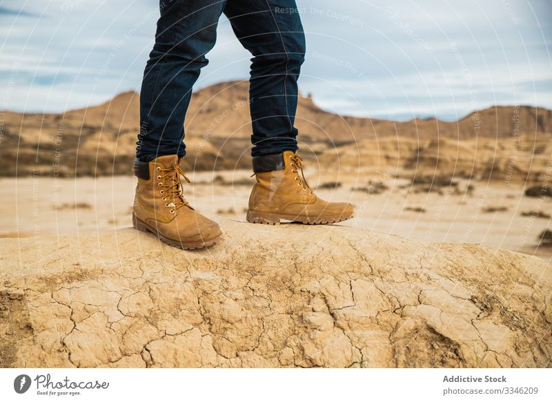 Anonymous tourist among desert with cliffs traveler tourism legs boots mountain jeans casual hill sky hiking trekking adventure nature vacation landscape