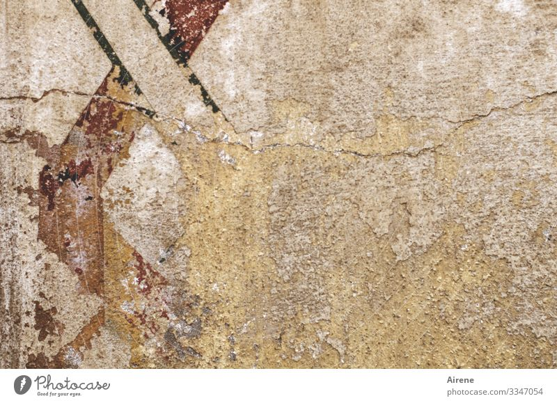 a lot of space on an old house wall, on the left fragments of old fresco painting Old Old building Facade crumble Rendered facade plaster Light brown
