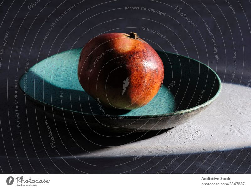 Ripe pomegranate on plate lit by ray of sunlight fruit still life organic natural single concrete exotic red fresh juicy beam health dessert agriculture diet