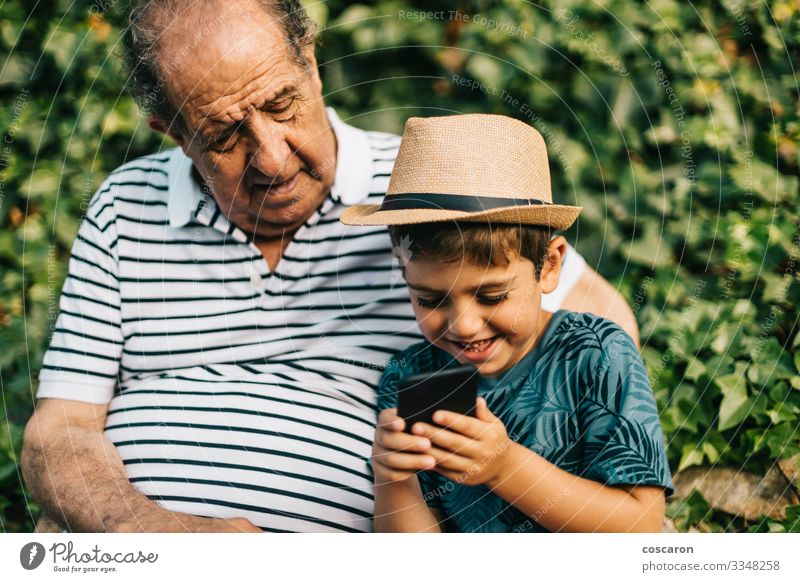 Grandfather and grandson playing with a mobile phone Lifestyle Happy Leisure and hobbies Playing Vacation & Travel Tourism Summer Summer vacation Child