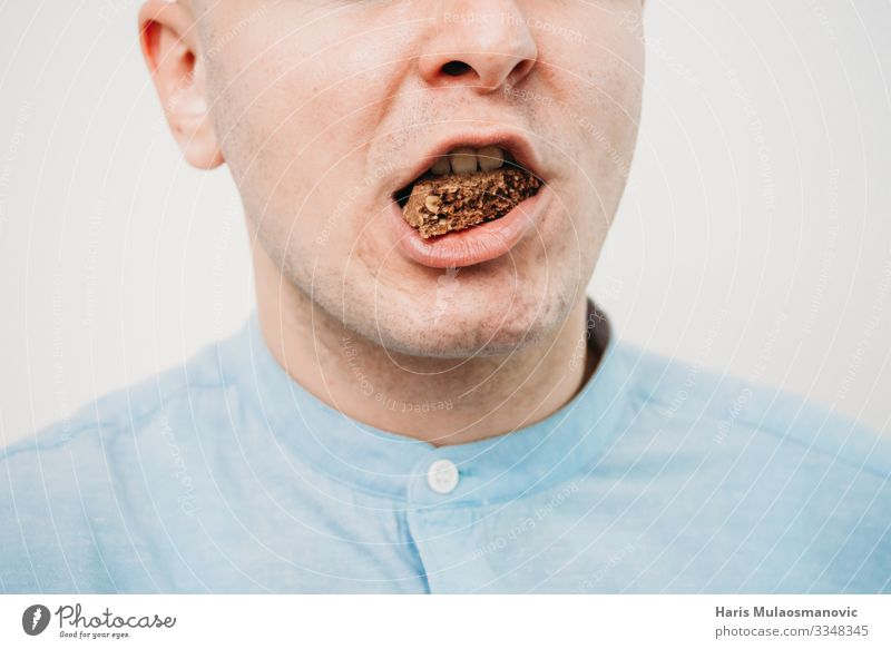 Man Eating chocolate close up Food Diet Feeding Candy Cookie Calorie Mouth Colour photo Interior shot Studio shot Copy Space left Copy Space right Flash photo