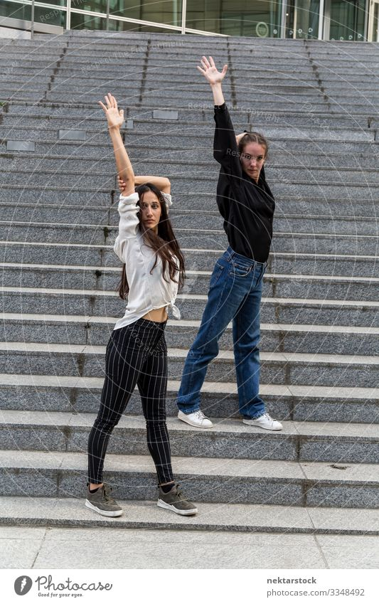 Two Women Posing on Steps with Arms Raised Woman Adults Youth (Young adults) Youth culture Contentment dancing girls steps arms raised staircase dancers
