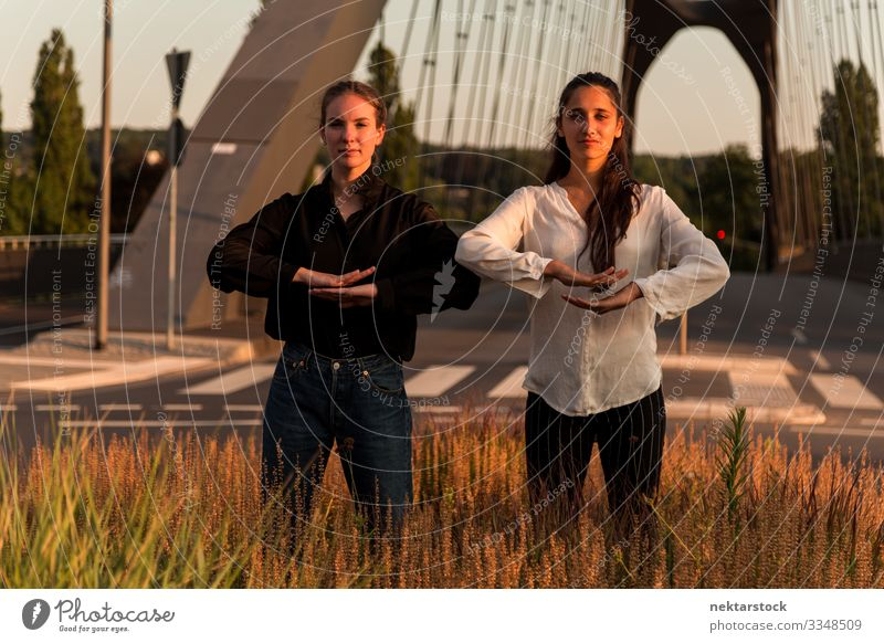 Two Women in Dance Poses on Roadside Grass Success Woman Adults Youth (Young adults) Contentment dancing girls pose hand sign Gesture dancers real life