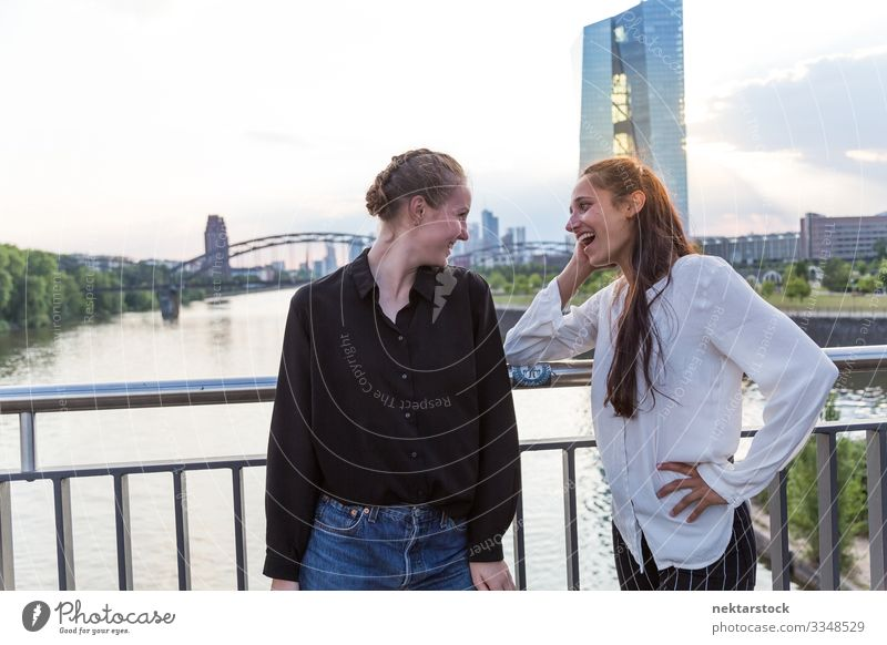 Two Women Making Eye Contact on Bridge with City Background Woman Adults Friendship Youth (Young adults) Skyline Smiling Love Happiness girls real life