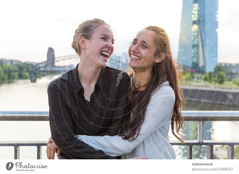 Girlfriends Embracing and Laughing on City Bridge Joy Happy Woman Adults Friendship Youth (Young adults) Youth culture Nature River High-rise Building Laughter