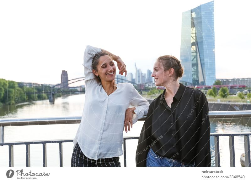 Girlfriends Smiling on City Bridge Over River Happy Woman Adults Friendship Youth (Young adults) Youth culture Nature High-rise Building girls eye contact