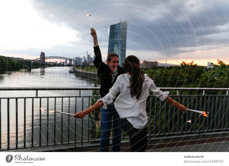 Young Women Sparkler Celebration on City Bridge 2 Joy Happy Feasts & Celebrations Woman Adults Youth (Young adults) Youth culture Sky River Skyline High-rise