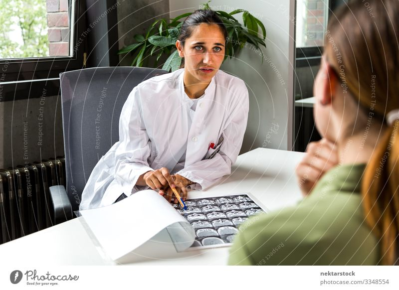 Young Medical Professional Showing CT Scan to Patient Health care Desk Doctor Office Career To talk Woman Adults Youth (Young adults) Honest Healthy patient