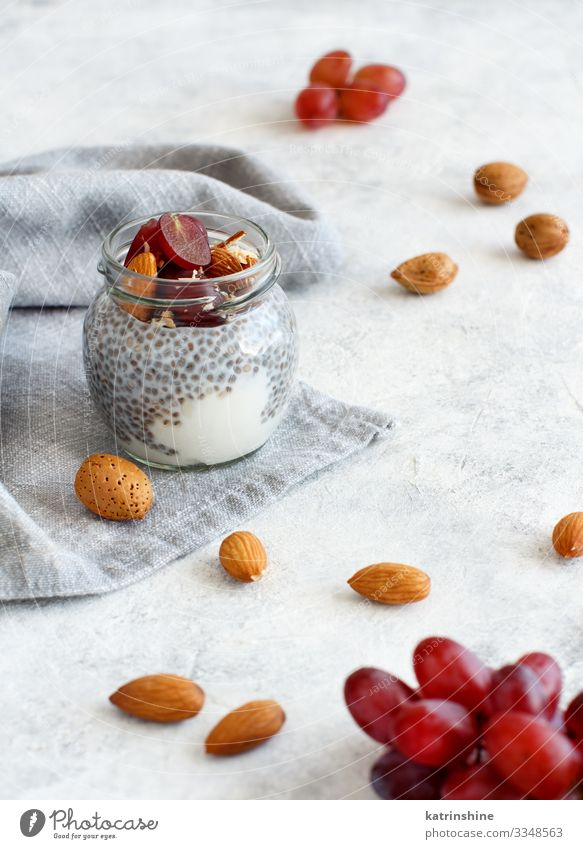 Chia pudding parfait with red grapes and almonds Yoghurt Fruit Dessert Eating Breakfast Diet Spoon White jar chia Bunch of grapes nuts Pudding seed chia seeds