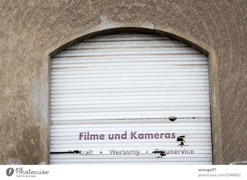 cessation of business Window Roller shutter Stone Plastic Characters Town Brown Gray Nostalgia Past Change Advertising Shutter Closed Film industry Camera