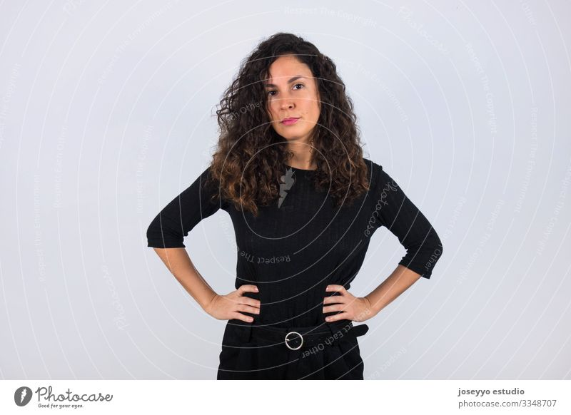 Curly haired brunette woman dressed in black with her hands on her waist looking at camera. 30-40 years advertisement attitude background beauty brown casual