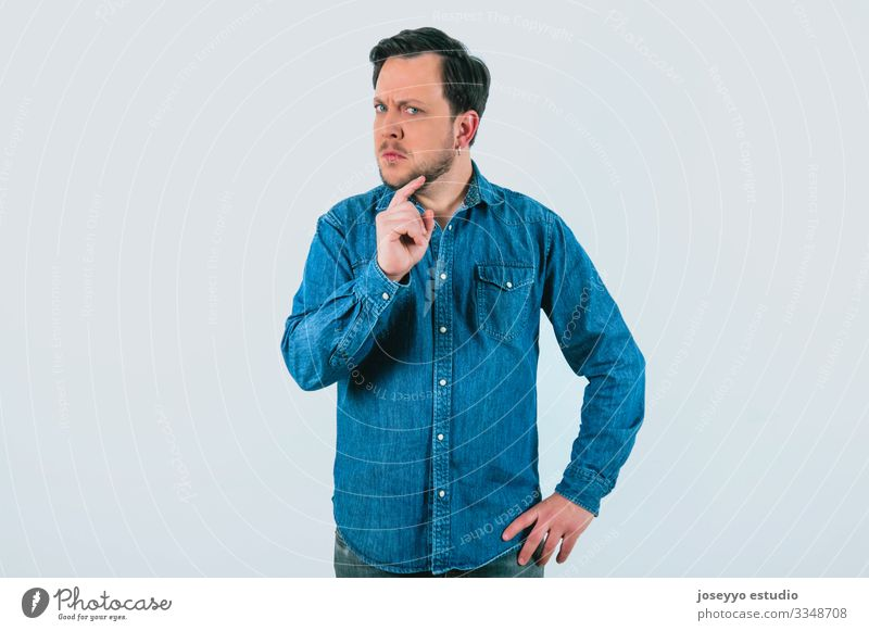 Young man with expression of disagreement and firmness. Denim shirt and isolated gray background. 30-40 years advertisement advertising analytical attitude