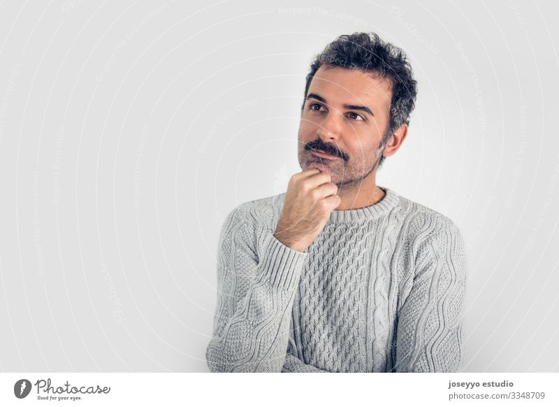 Portrait of  handsome and brown thinking man with mustache and  gray sweater. Gray background. Copy space adult arms attractive brain casual challenge