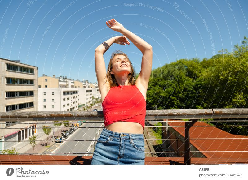 Young beautiful woman sunbathing on a bridge over the city Lifestyle Joy Happy Beautiful Relaxation Leisure and hobbies Summer Sun Woman Adults
