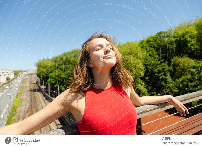 Young beautiful woman sunbathing on a bridge over the city Lifestyle Joy Happy Beautiful Relaxation Leisure and hobbies Summer Sun Sunbathing Woman Adults