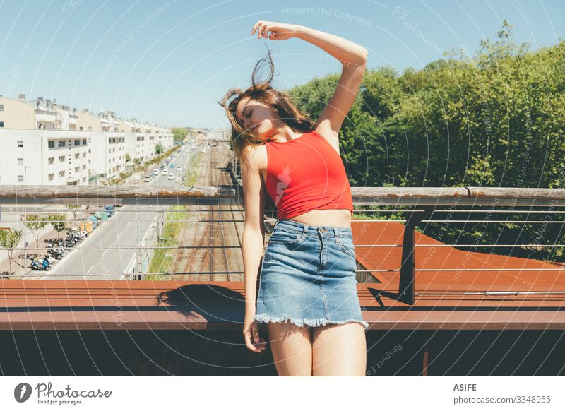 Young beautiful woman sunbathing on a bridge over the city Lifestyle Joy Happy Beautiful Relaxation Leisure and hobbies Summer Sun Woman Adults Arm Nature Wind