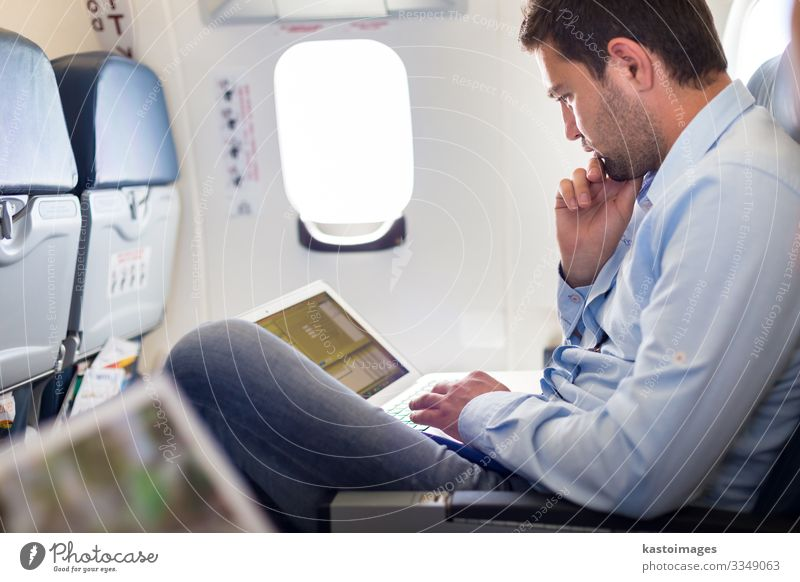 Businessman working with laptop on airplane. Lifestyle Reading Vacation & Travel Trip Work and employment Economy Computer Notebook Human being Man Adults Hut