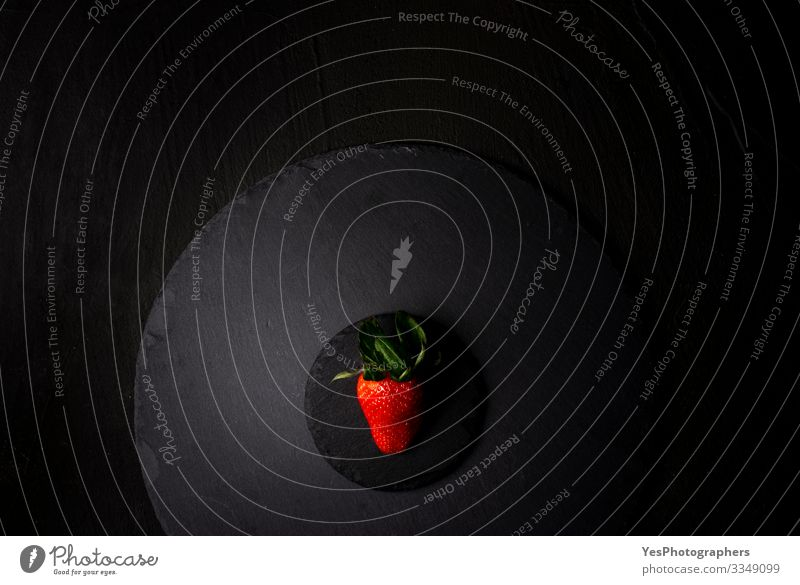 Single strawberry on a black granite plate. Above view Fruit Dessert Organic produce Diet Fresh Delicious Natural above view Berries black plate flat lay food