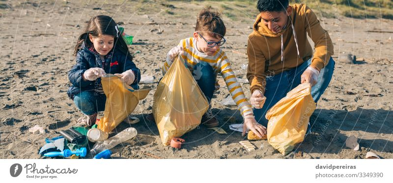 Young volunteers cleaning the beach Woman Child Human being Man Beach Adults Environment Happy Boy (child) Group Sand Dirty Smiling Internet Plastic Trash
