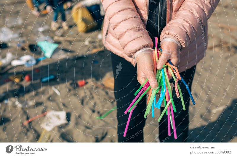 Woman showing handful of straws collected on the beach Human being Hand Beach Adults Environment Family & Relations Copy Space Group Work and employment Sand