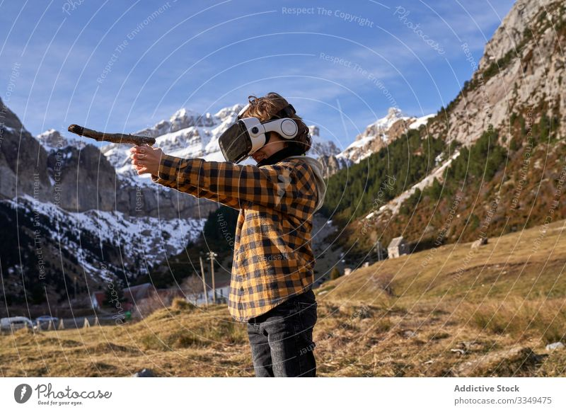 Boy standing on stone in VR glasses against mountain boy vr nature valley virtual stick reality headset modern device entertainment explore terrain technology