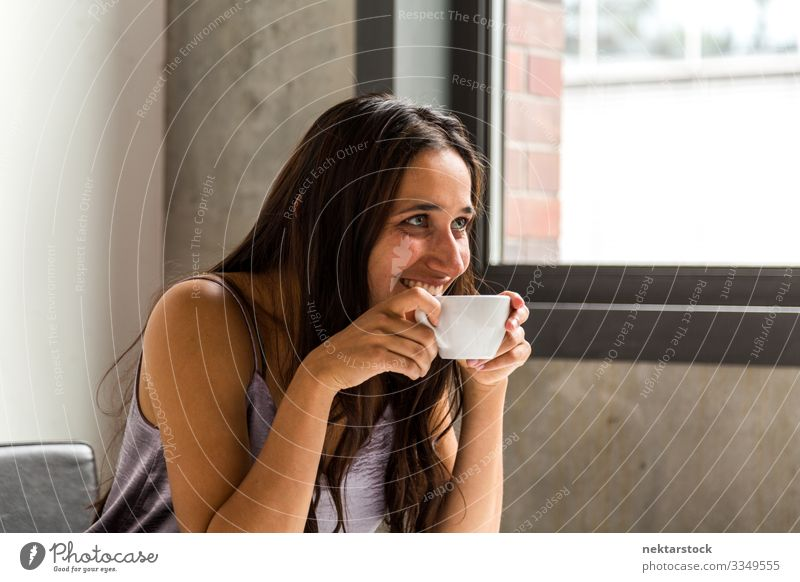 Young woman having a coffee break in office. Side view. Coffee Tea Work and employment Profession Workplace Office Woman Adults Youth (Young adults) Smiling Sit