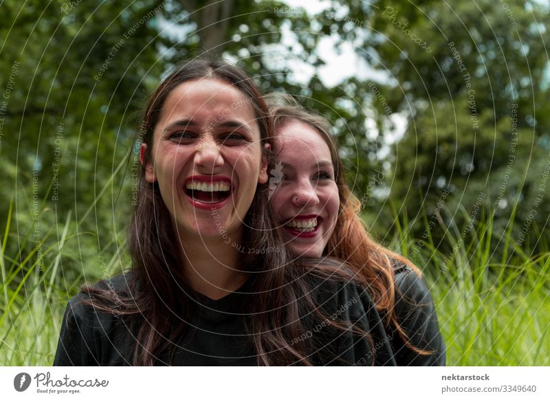 Two Girlfriends of Different Races Laughing Outdoors Joy Beautiful Woman Adults Friendship Youth (Young adults) Nature Grass Park Embrace Happiness Together