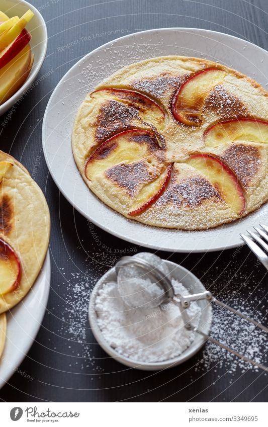 Pancakes with apple and icing sugar on white plate Apple Dough Baked goods Candy Confectioner`s sugar Slice of apple Sugar Nutrition Organic produce Food